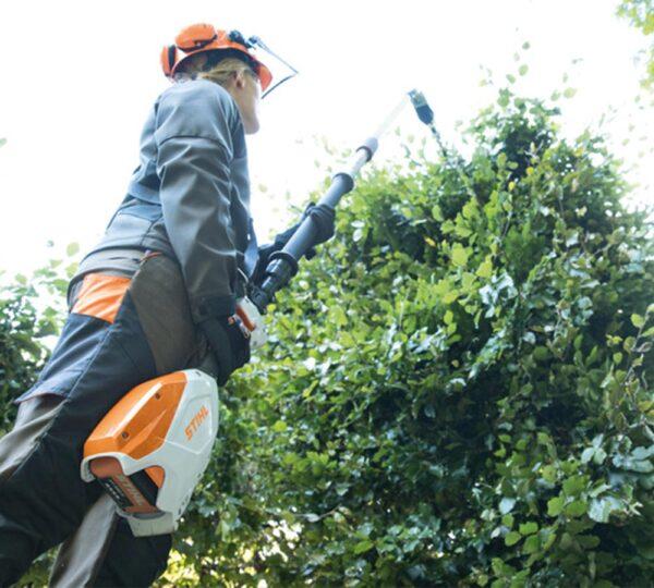 miljöbild av en man som klipper häck med stånghäcksax från Stihl
