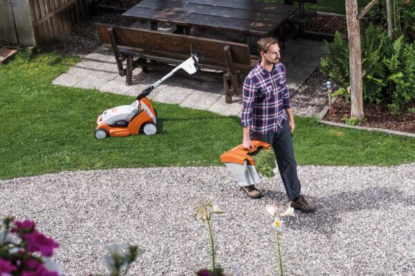 en man ska tömma gräsklipparen