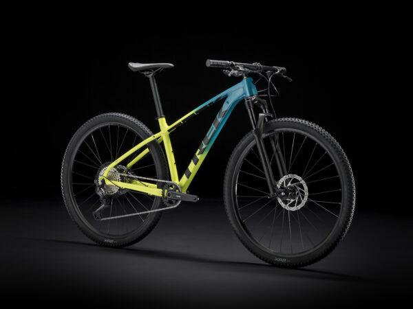 Studiobild på TREK cykel X-caliber 9. en gul och blå cykel mot svart bakgrund.