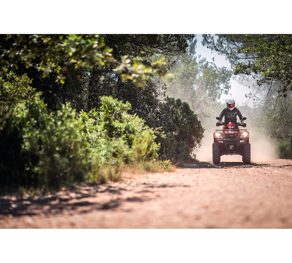 Förare kör fyrhjuling på grusväg sommarbild