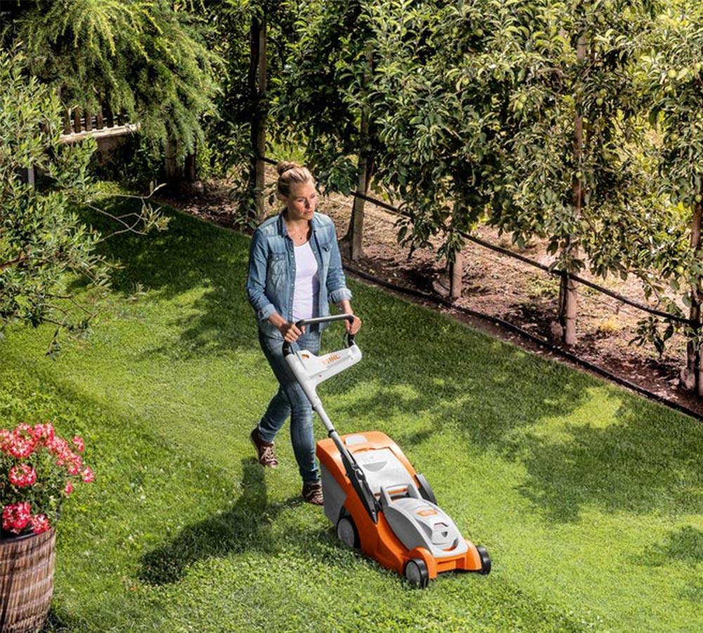 Ung kvinna klipper gräset med batteriklippare från Stihl