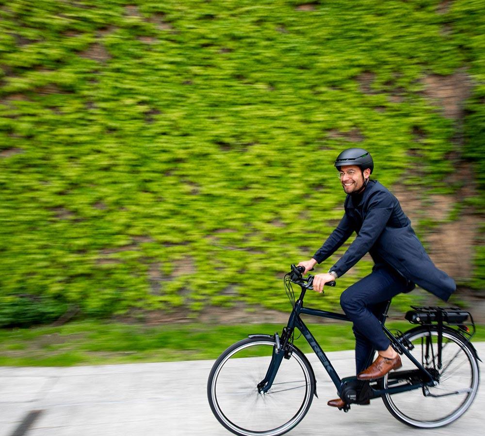 man cyklar elcykel med grön hög häck i bakgrunden